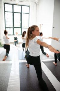 Mehrere Frauen üben auf ihren hejhej-mats Yogamatten eine Vartion des Warrior one in einer Yogastunde.