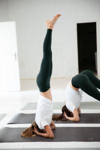 Zwei Frauen üben einen Handstand auf ihren dunklen hejhej-mats Yogamatten.