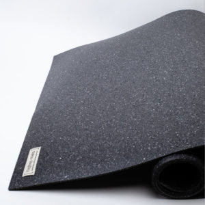 The dark hejhej-mat half rolled up, you can see the mosaic pattern of the yoga mat very well