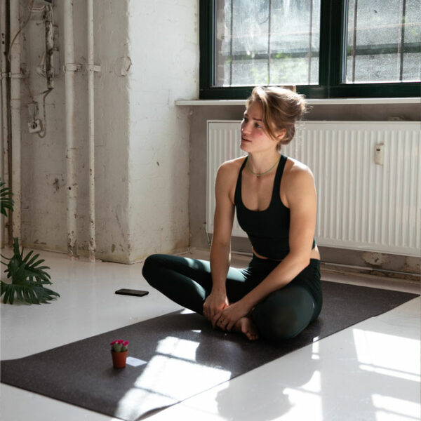 A yoga teacher sits on the rather dark recycled hejhej-mat before class.