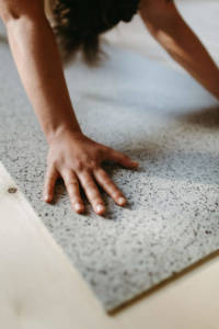 Close-up of hands in the downward facing dog on the bright hejhej-mat.