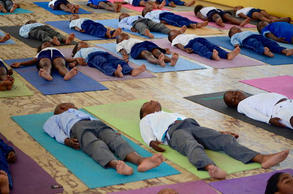 many children relaxing on their yoga mats - with our eco-friendly yoga mat we support the NGO Earth Child Project