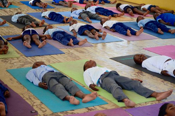 viele Kinder liegen auf ihrer Yogamatte und machen die Endentspannung im Yoga - durch unsere umweltfreundliche Yogamatte können wir genau das ermöglichen