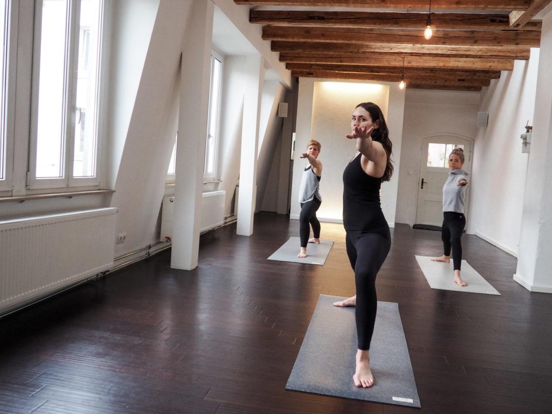 drei Yogis im Krieger zwei - eine Yogamatte kann ein super nachhaltiges Weihnachtsgeschenk für Yoga sein
