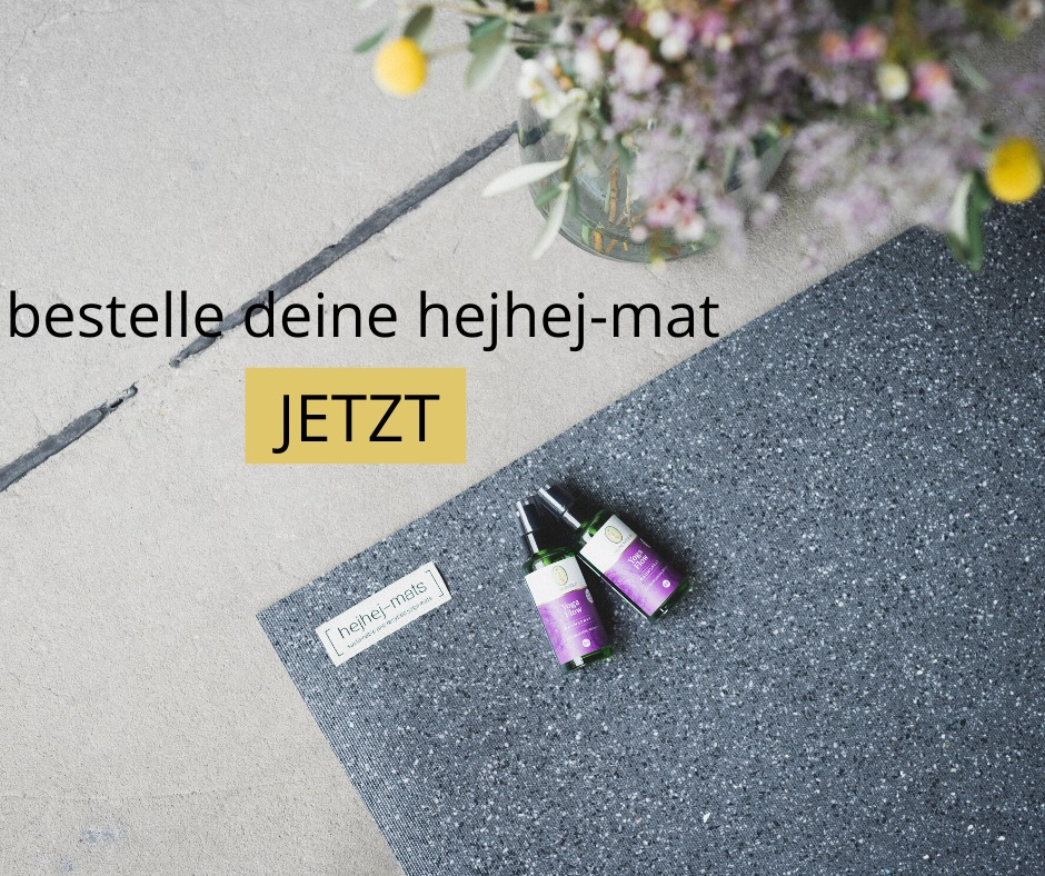 Auf der dunklen hejhej-mats Yogamatten liegen zwei ökologische Yogamattensprays von Primavera.
