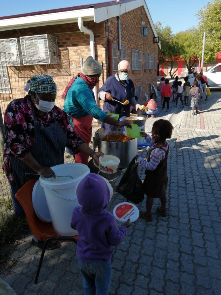 Kinder holen ihr Essen ab und nehmen es in Box mit nach Hause