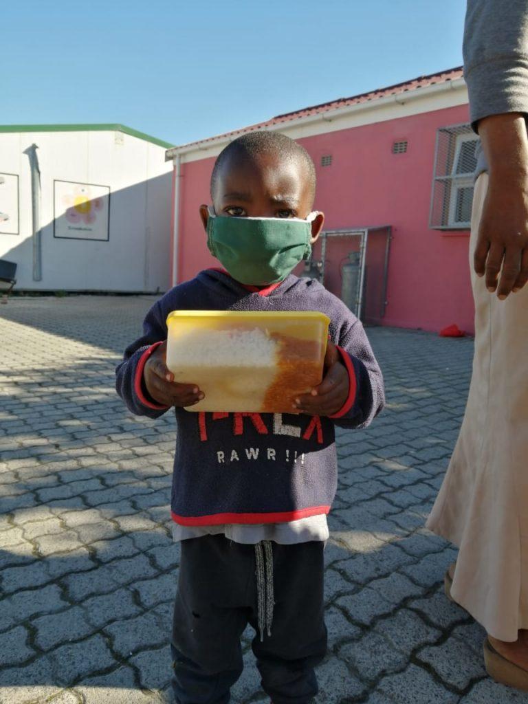 kleiner Junge mit Mundschutz und abgeholter Essensspende