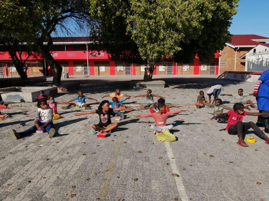 Die ECP Kinder mit Sicherheitsabstand vor ihrer Schule