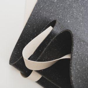 Der hejhej-strap schlängelt sich entlang der dunklen hejhej-mat im Set aus Yogagurt und Yogamatte.