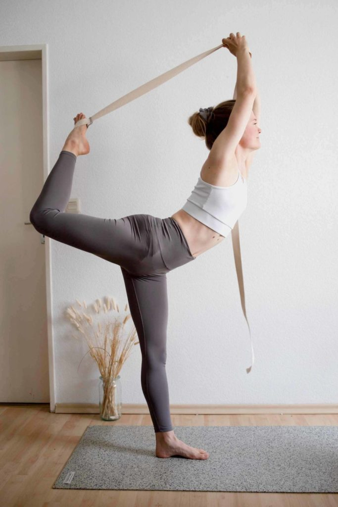 Sophia stands in the dancer's asana and uses the yoga strap to pull her left leg even further towards her head.