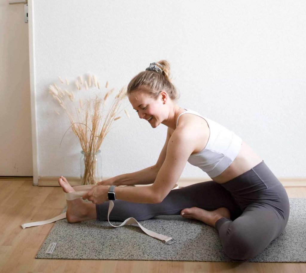 Sophia in the forward bend with the right leg, yoga strap serves as an extension of the arms