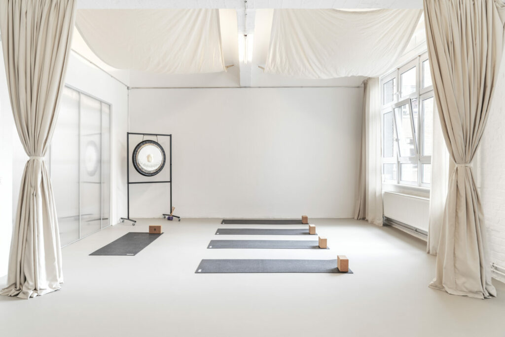 The dark hejhej-mats lie in order on the floor in a minimalist light room.