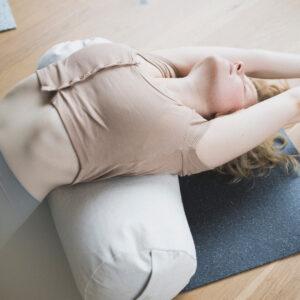 Ein blondes Mädchen streckt sich am Boden - der hejhej-bolster liegt unter dem oberen Teil ihres Rückens und bietet support.