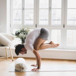 Ein Yogi übt die Yogapose Krähe. Der hejhej-bolster liegt vor ihm und dient als Sicherheit, falls er vorne über fällt.