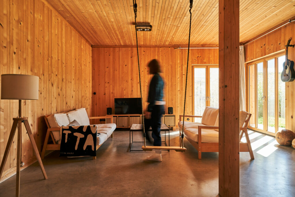 Wooden house interior with cosy atmosphere and a woman walking through the room