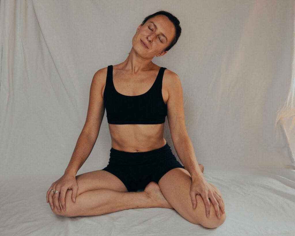 Marta sitzt und dehnt Nacken und Schulter