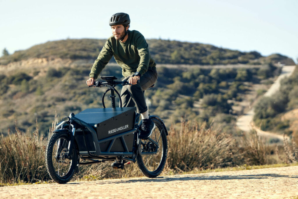Ein Mann auf einem Cargo-bike von Riese & Müller fährt durch eine schöne Landschaft