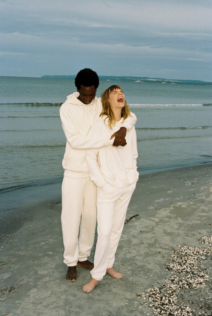 Man and woman stand hugging on the beach wearing the undyed collection by Armedangels