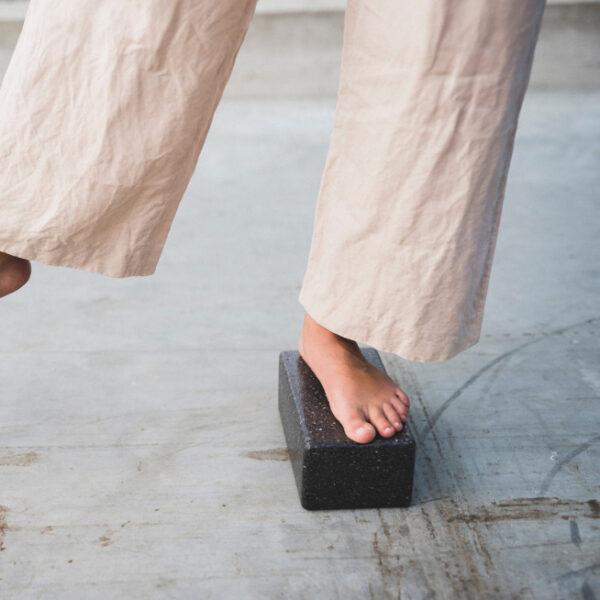 Ein Mädchen steht mit einem Bein auf einem Yogablock.