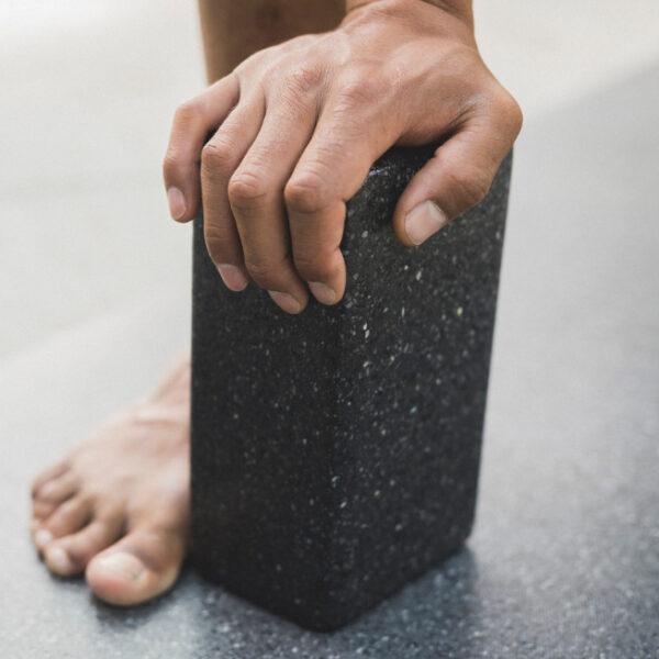Jemand stützt sich auf einem nachhaltigen Yogablock mit der Hand ab.