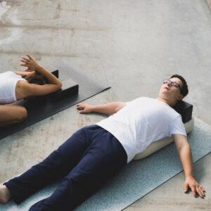 Zwei Yogi:nis üben Yoga liegend auf der Matte und haben als Hiflsmittel einen nachhaltigen Yogablock.